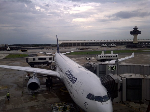 "A view of Washington Dulles International Airport, including the iconic main terminal designed in the late 1950s and the infamous ""mobile lounges"" that I think look more like aliens (the weird rubber-tired vehicles behind the Lufthansa plane)."