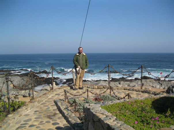 Alex standing in front of the grave site, with the ocean view behind. Even the site has been designed to look like the prow of a ship, with sails above.