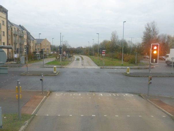 "The start of the busway on the edge of town, near some new-style apartment complexes. Note the marking indicating the roadway is for ""GUIDED BUS"" only."