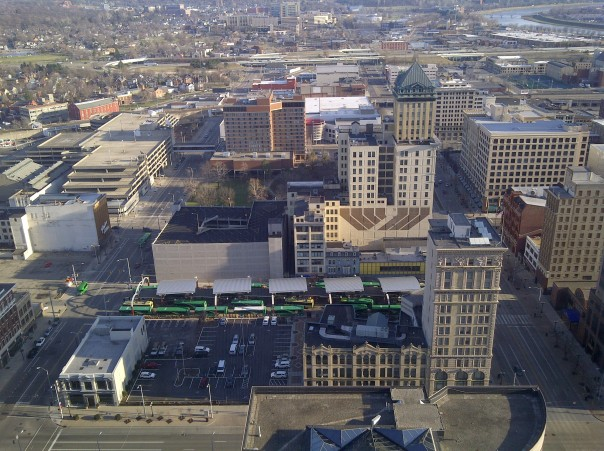 This is downtown Dayton, Ohio - looking out over Wright Stop Plaza, the downtown transit center, from the top of a tall building. See the green buses? This is the evening line-up, when buses from most routes all come together at once to allow transfers and then depart (a moment after this they start to pull out like a long green snake!). This particular transit center is special because it has trolley wire and serves trolley buses...despite being a smaller city and transit system Dayton is one of only five US cities to have any trolley buses remaining.